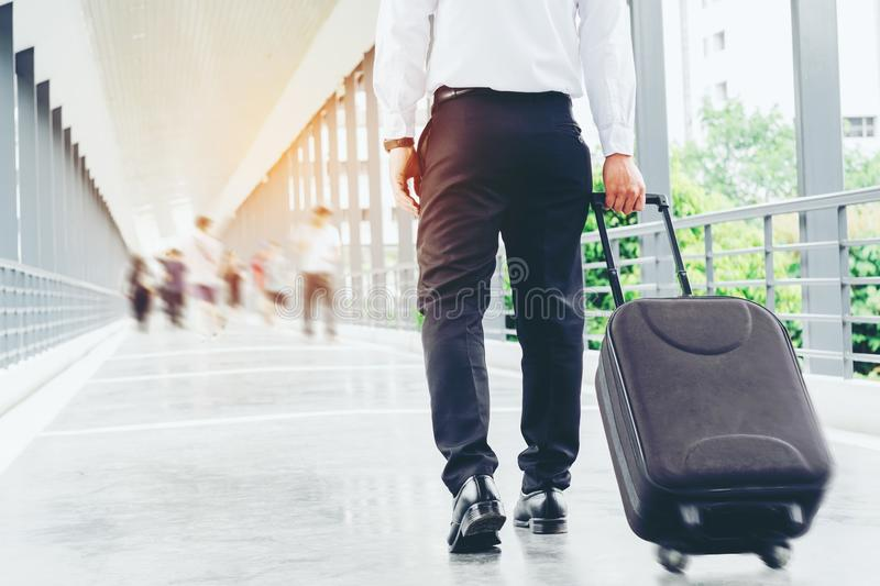 Businessman holding trolley bag going up on travel royalty free stock images