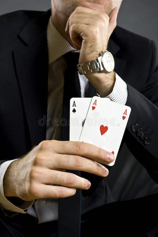 Businessman holding two aces stock photo