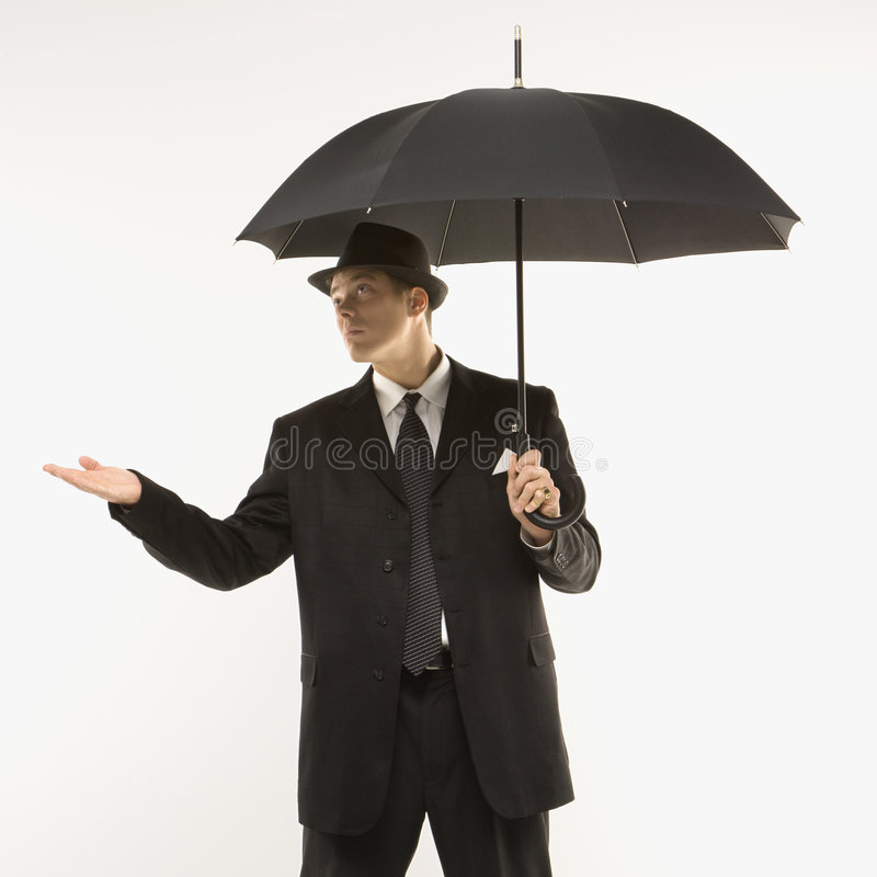 Businessman holding umbrella. Caucasian mid-adult businessman wearing fedora holding umbrella with arm outstretched stock photos