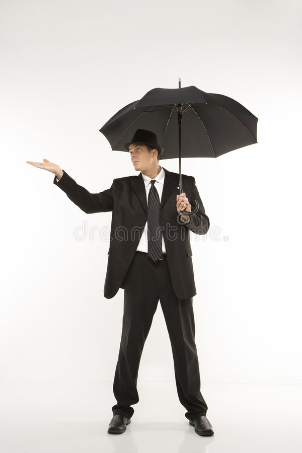 Businessman holding umbrella with hand held out. Caucasian mid-adult businessman wearing fedora holding umbrella with arm outstretched royalty free stock image