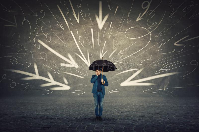 Businessman holding umbrella, looking down confused, being under pressure as multiple arrows on the wall pointing to him blaming royalty free stock photography