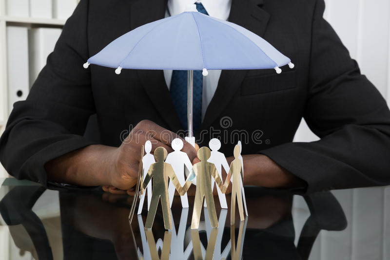Businessman Holding Umbrella Over Paper Cutout People. Close-up Of Businessman Hands Holding Small Umbrella Over Paper Cutout People At Desk stock photography