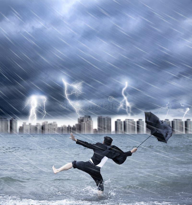 Businessman holding an umbrella with thundershower stock image