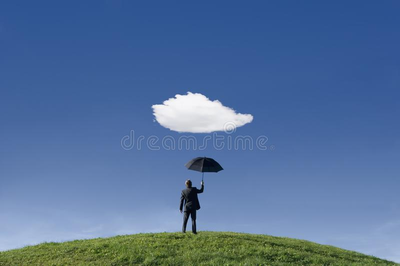 Businessman holding umbrella underneath a single cloud. Businessman on a hill holding umbrella underneath a single cloud themes of anticipation protection out of stock photo