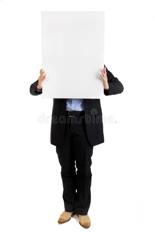 Businessman holding up a blank sign. Businessman holding up a blank white rectangular sign or placard with copyspace for your text in front of his face royalty free stock photography