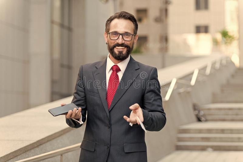A businessman holding up credit card and making online payment on his cellphone with building background. happy businessman stock images