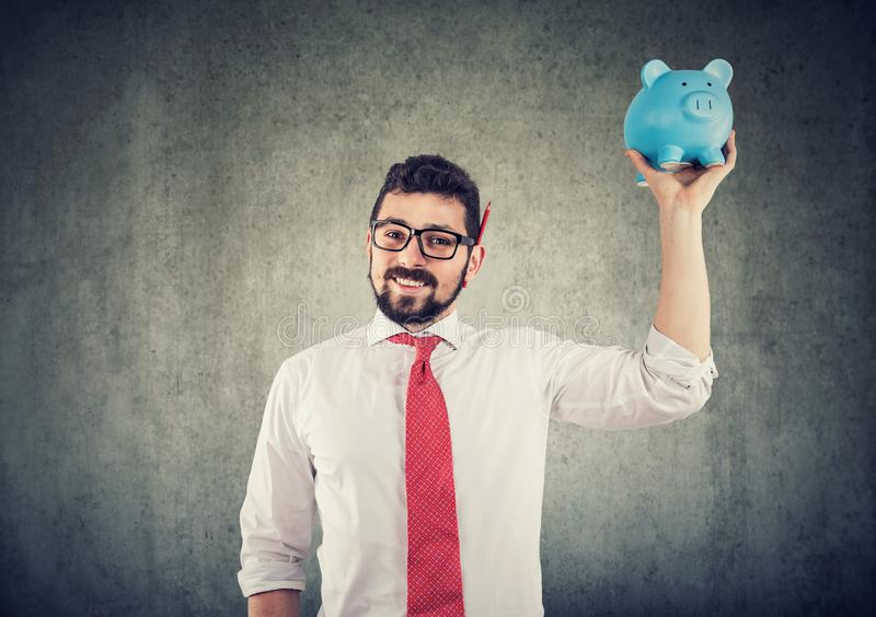 Businessman holding up a piggy bank royalty free stock photo