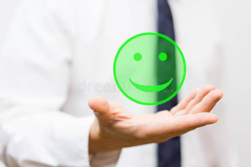 Businessman is holding virtual smiley in his hand, concept of ha stock photo