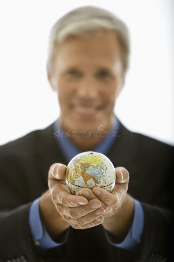 Businessman holding world. stock photo