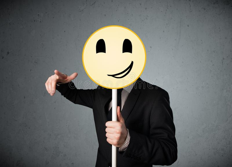 Businessman holding a smiley face emoticon. Businessman holding a yellow smiley face emoticon in front of his head stock photography