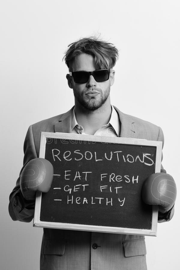Businessman holds blackboard with sign pointing healthy lifestyle resolutions. Boxer in formal costume with serious face. Health and fitness concept. Man in stock photography