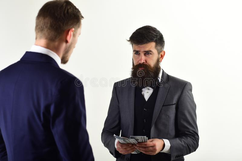 Businessman holds bunch of dollars. Men in formal suits meet for business deal. Guy pays with cash money. Financial deal royalty free stock images