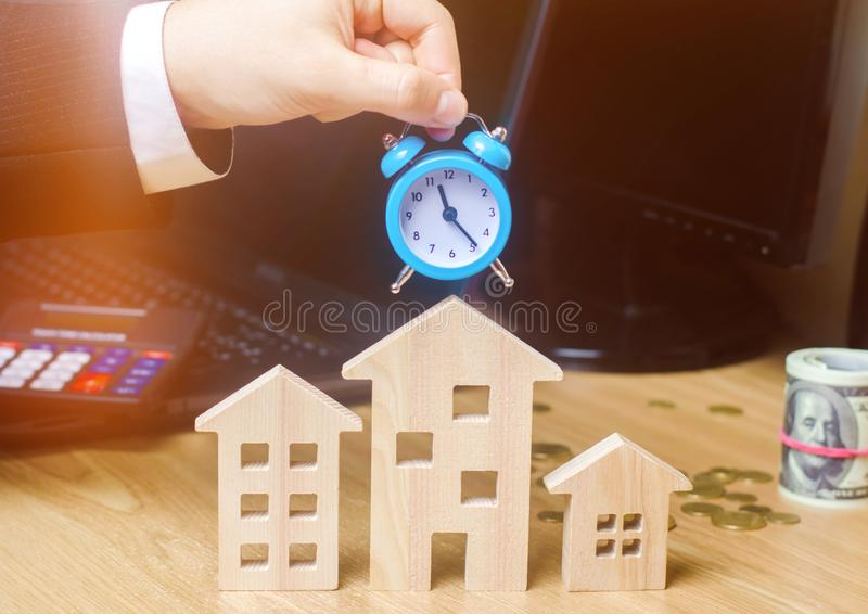 Businessman holds clock over wooden houses. Time to pay taxes. Mortgage. Payment of debts for real estate. Payment of utility royalty free stock photos