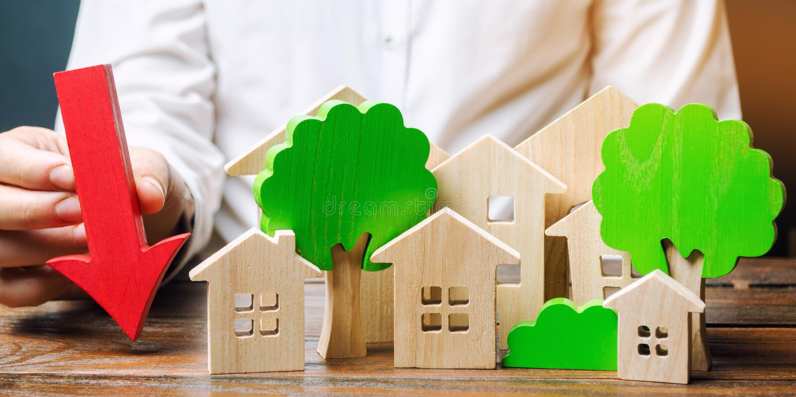 Businessman holds down arrow near wooden houses and trees. The concept of reducing investment in the construction of new buildings stock images