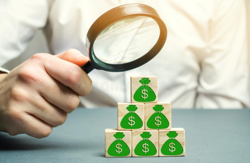 Businessman holds magnifying glass over cubes with dollars. Analysis of profits and revenues in the company. Distribution of money royalty free stock photo