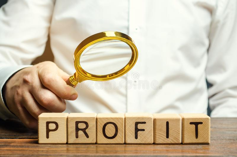 Businessman holds a magnifying glass over the word Profit. The concept of profitability and performance of business. Analysis of stock photography