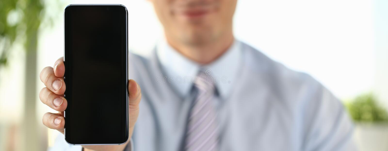 A businessman holds a new smartphone stock image