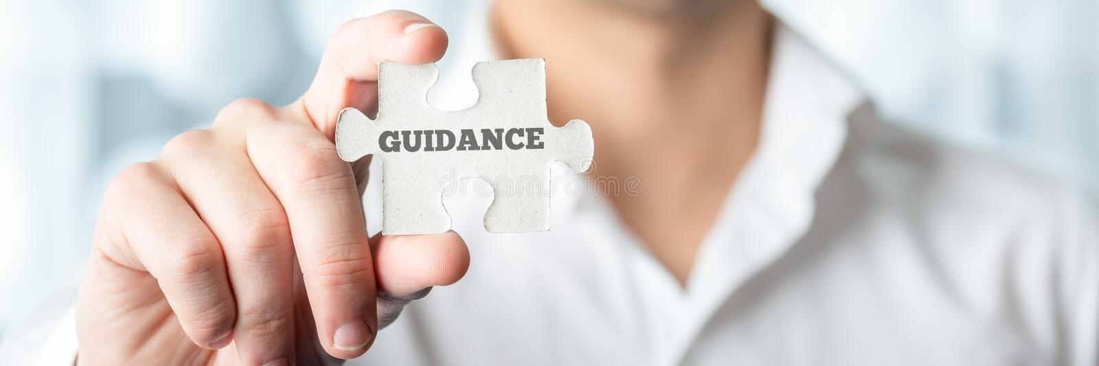 Businessman Holds Puzzle Piece with Guidance Text. Close up Businessman Hand Holding Puzzle Piece with Conceptual Guidance Text In Front of the Camera stock images
