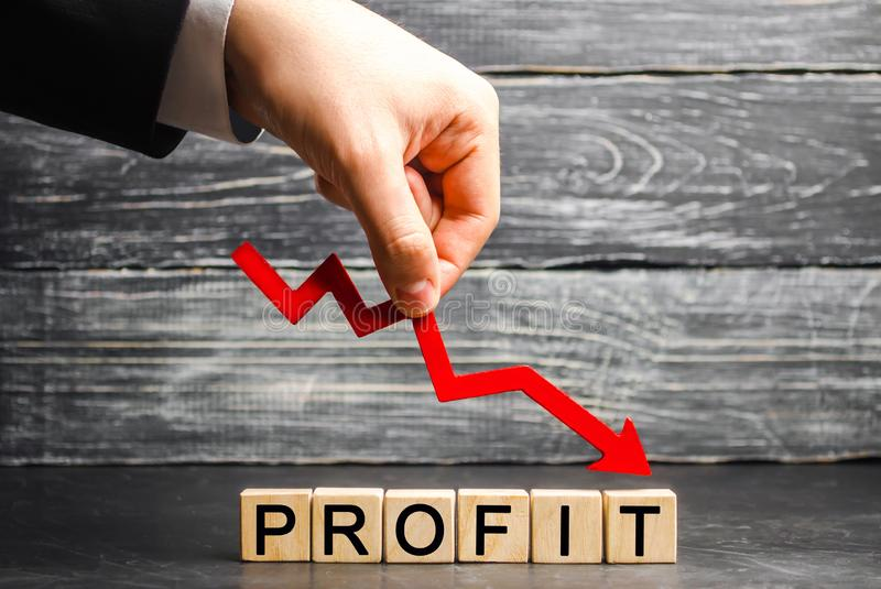A businessman holds a red arrow to down and the inscription `profit`. Unsuccessful business and poverty. Profit decline. Loss of i. Nvestment. Low wages royalty free stock photo