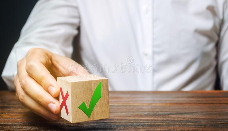 Businessman holds a wooden block with a green check mark. The concept of choice and making the right decision. Business management stock photos