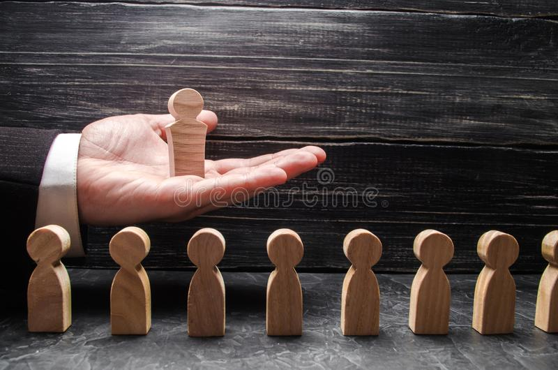 A businessman holds a wooden leader figure on the palm of his hand over a number of other workers. Concept leader, team work. stock photos