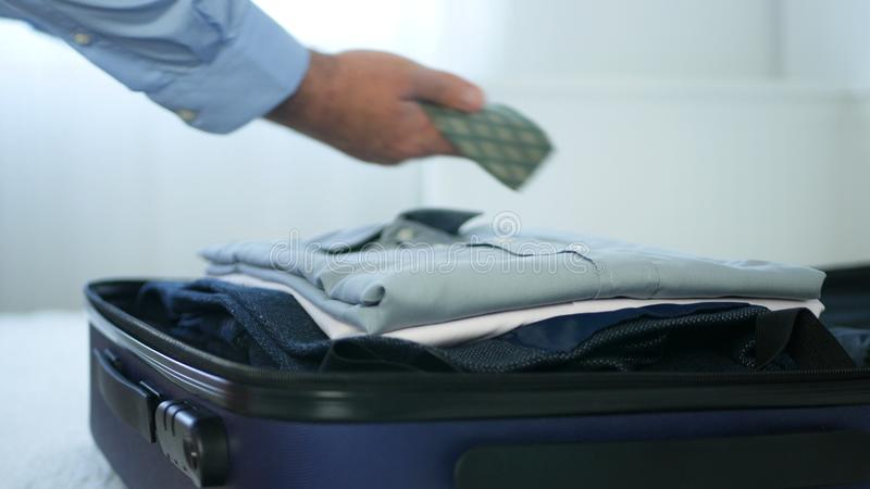 Businessman in a Hotel Room Put Clean Clothes in Suitcase for Travel.  royalty free stock images