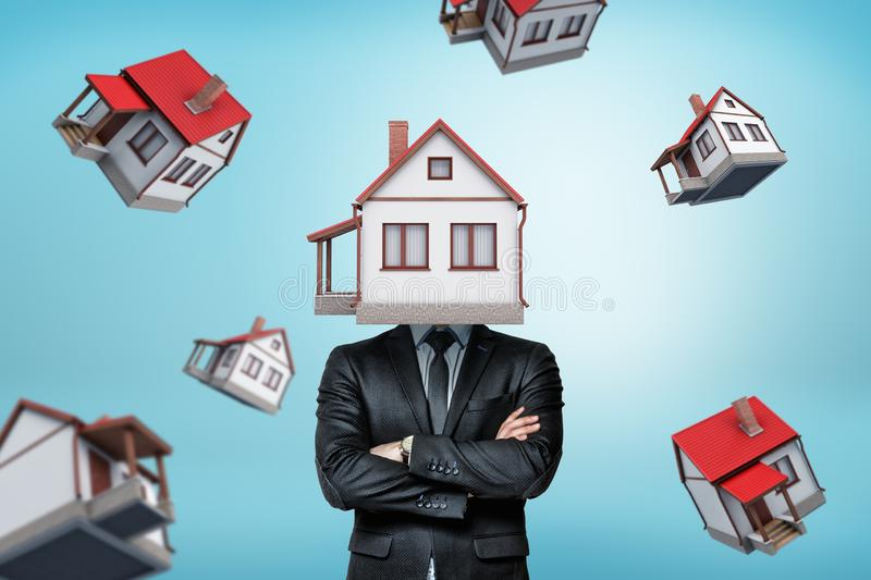 A businessman with a house instead of his head stands with folded arms on a background with many other houses. Real estate agent. Home insurance. Buying royalty free stock images