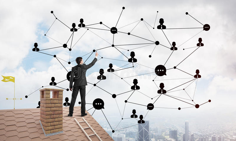 Businessman on house roof presenting networking and connection concept. Mixed media. Young man standing with back on roof and drawing connection lines. Mixed royalty free stock image