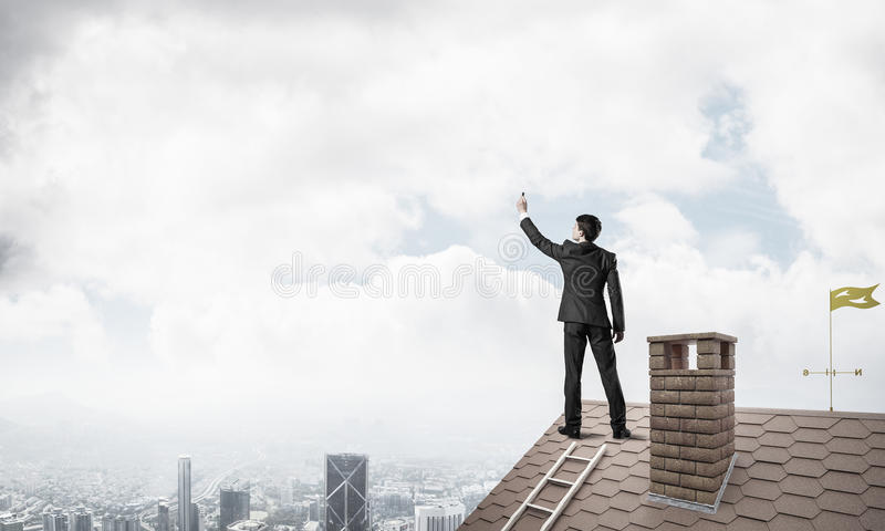 Businessman on house roof touch empty space. Mixed media. Young man standing with back with marker. Mixed media stock photo