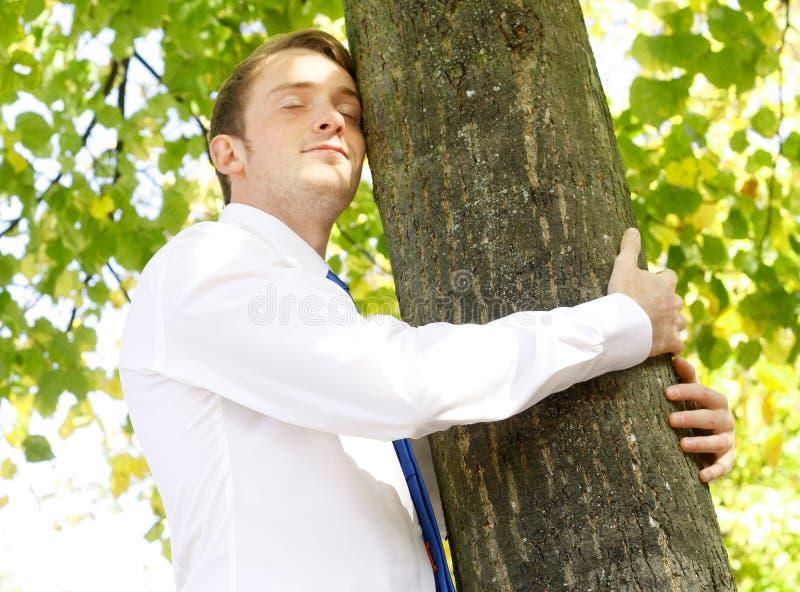 Businessman hugging tree