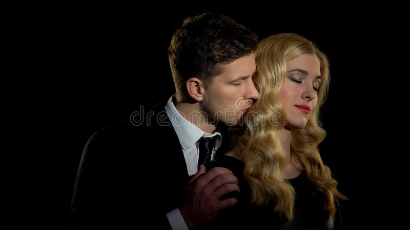 Businessman hugging young mistress from behind, secret relationship, love royalty free stock photography