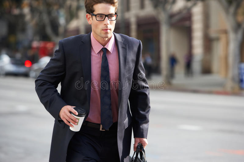 Businessman Hurrying Along Street Holding Takeaway Coffee royalty free stock photography