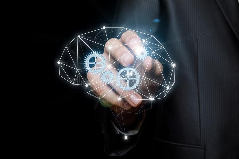 Businessman inserts the gear into the mechanism of thinking . stock photo