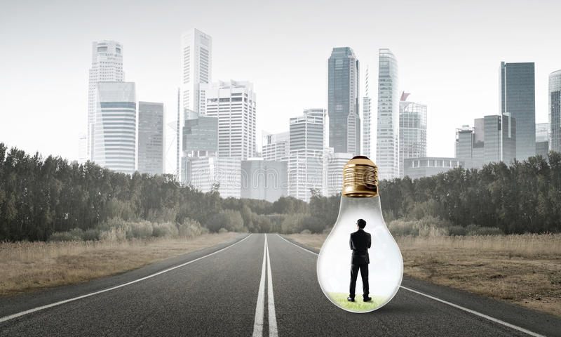 Businessman inside light bulb. Young businessman trapped inside of light bulb on asphalt road royalty free stock image