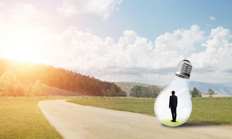 Businessman inside light bulb. Young businessman trapped inside of light bulb on countryside road royalty free stock photo