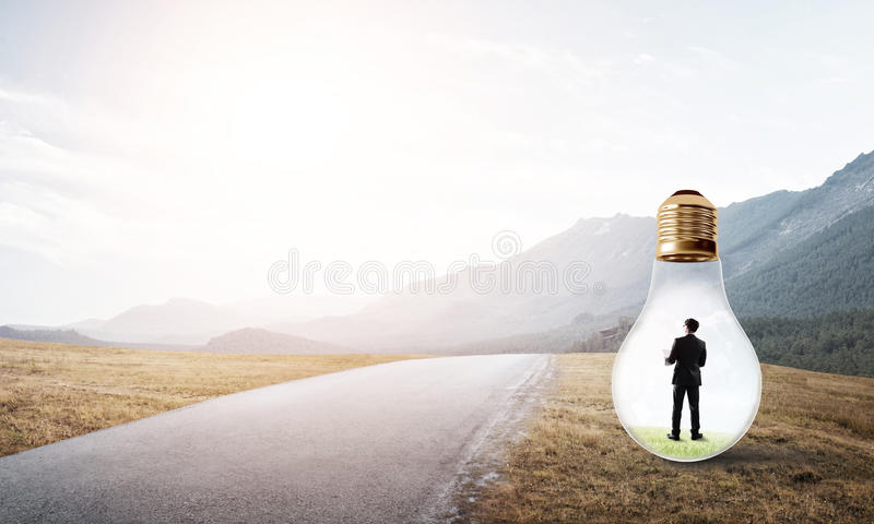 Businessman inside light bulb. Young businessman trapped inside of light bulb on countryside road royalty free stock images