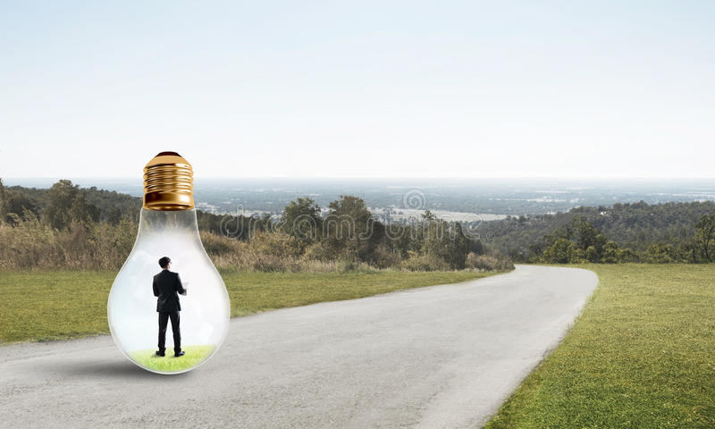 Businessman inside light bulb. Young businessman trapped inside of light bulb on countryside road stock photography