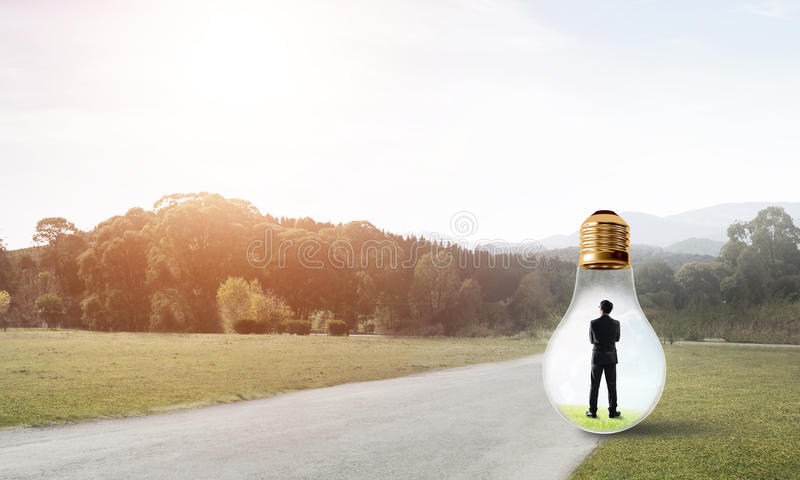 Businessman inside light bulb. Young businessman trapped inside of light bulb on countryside road royalty free stock image