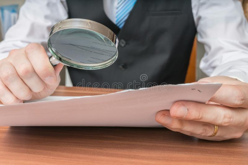 Businessman is inspecting contract with magnifying glass.  stock photography