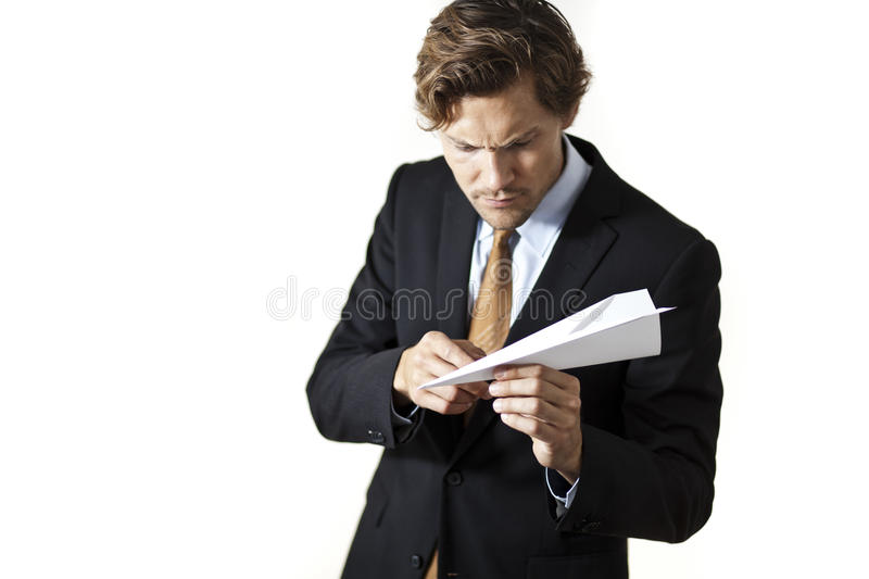Businessman inspecting paper airplane stock image