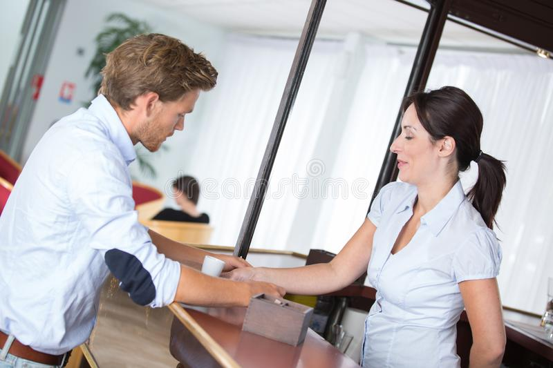 Businessman interacting with pretty receptionist at hotel. Businessman interacting with pretty receptionist at the hotel stock photography