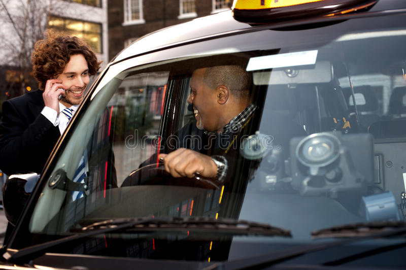 Businessman interacting with taxi driver. Taxi cab driver communicating with male passenger stock photo
