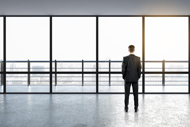Businessman in interior. Back view of thoughtful businessman looking out of window in modern empty office interior with panoramic city view and sunlight on royalty free illustration
