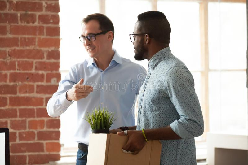 Businessman introduce black newcomer to company team. Middle-aged businessman introduce African American male worker to colleagues, smiling boss acquaint company royalty free stock photography