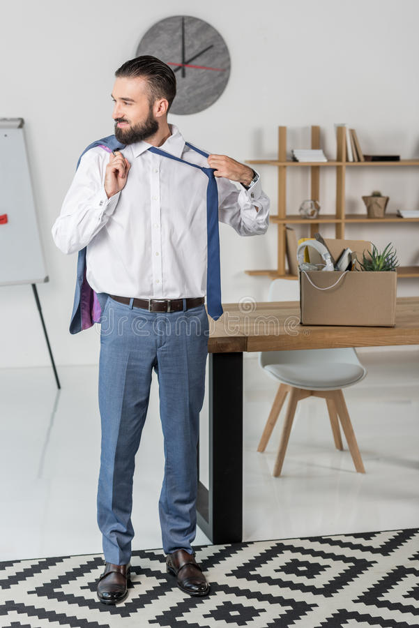 Businessman with jacket in hand untying tie in office, quitting job concept. Smiling businessman with jacket in hand untying tie in office, quitting job concept royalty free stock photo