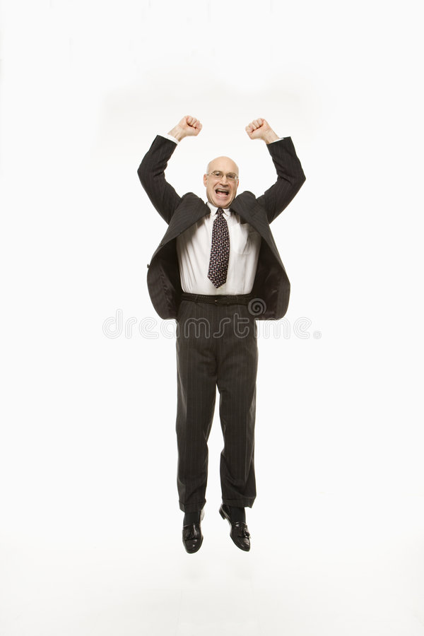 Businessman jumping with arms raised. stock images