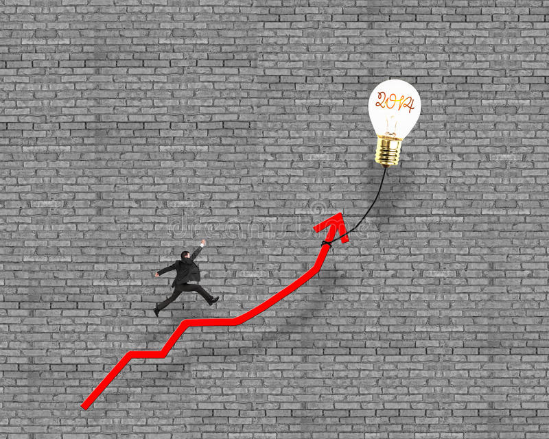 Businessman jumping on growth red arrow with glowing lamp balloon. Bricks wall background royalty free stock photography
