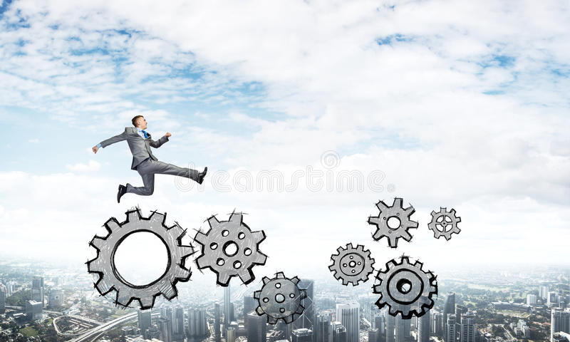 Businessman jumping high. Young businessman against city background running in a hurry royalty free stock image