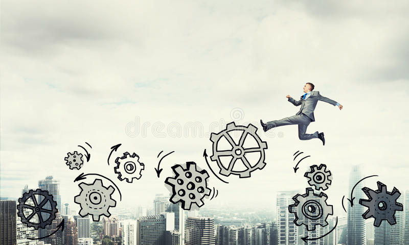 Businessman jumping high. Young businessman against city background running in a hurry royalty free stock photo
