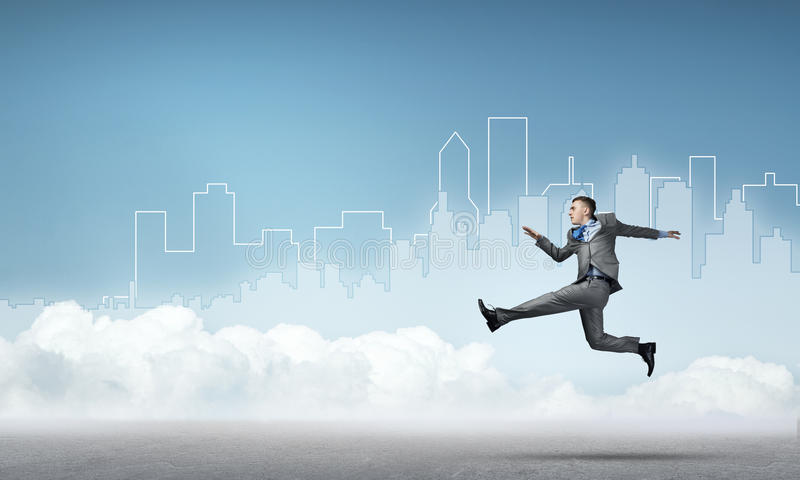 Businessman jumping high. Young businessman against city background running in a hurry royalty free stock images